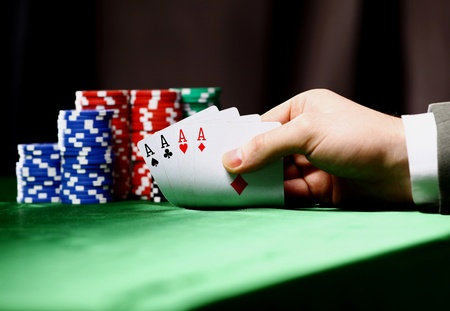 games hand: Poker chips and a hand flip the cards isolated against green felt Stock Photo