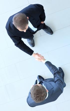 manos unidas: Vista superior de un hombre de negocios dos que sacude las manos - Bienvenido a business Foto de archivo