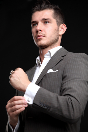 elegant young fashion man looking at his cufflinks while fixing them photo