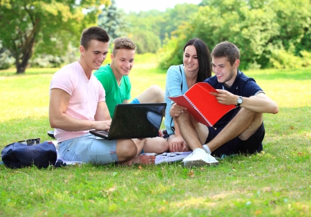 four smiling student studying in green park photo