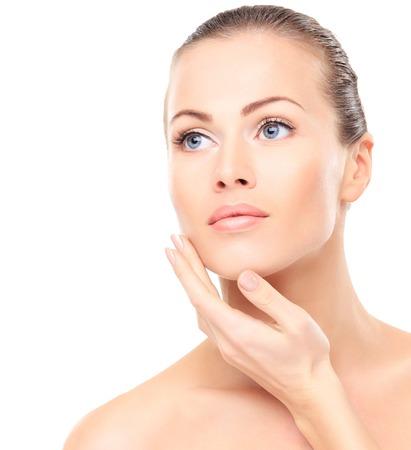 gezichtsbehandeling: Mooi meisje wat betreft haar gezicht Stockfoto