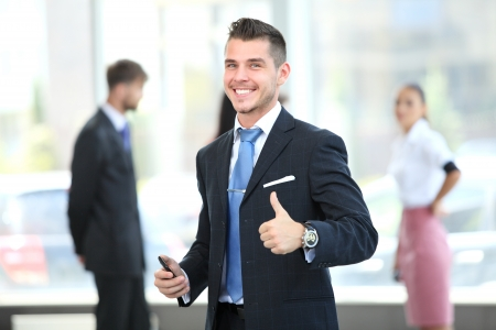 Happy smiling young business man with thumbs up gesture photo