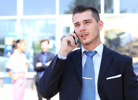 휴대 전화에 얘기하는 행복 성공적인 젊은 비즈니스 사람 (남자)