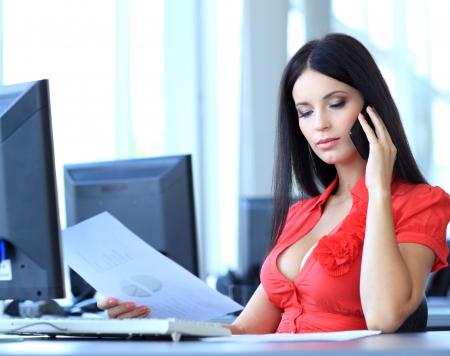young business woman reading sitting at the desk on office background photo