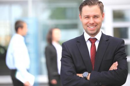 üzlet: Boldog okos üzletember a csapattársaival megbeszélése a háttérben