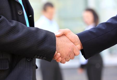 pacto: Primer plano de los hombres de negocios dándose la mano sobre un acuerdo