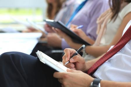 meeting room: Closeup of executive writing notes during business meeting Stock Photo