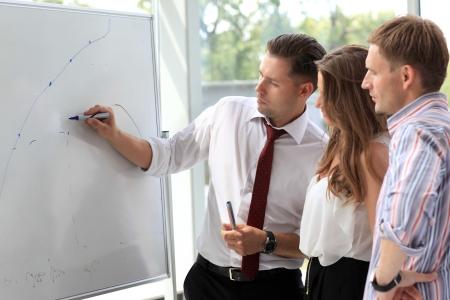 그녀는 화이트 보드에 뭔가 설명하는 동안 그들의 지도자를 찾고 사업 사람들