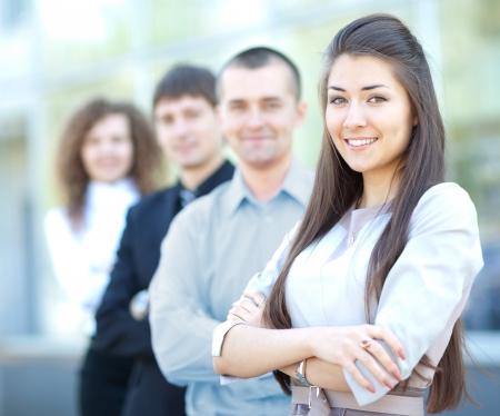 companionship: Un equipo de negocios con bastante líder delante mirando la cámara y sonriendo Foto de archivo