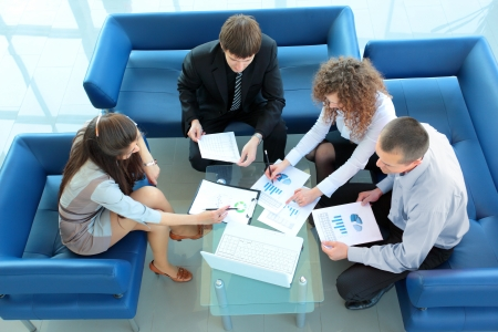 interacting: Top view of working business group sitting at table during corporate meeting Stock Photo
