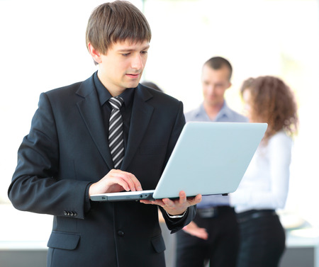 Portrait of a smart business man using laptop with colleagues in the background photo