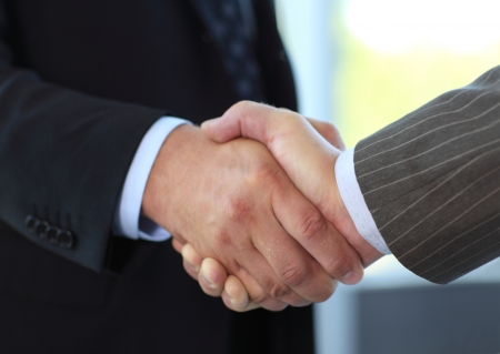 business handshake: Closeup of business people shaking hands over a deal