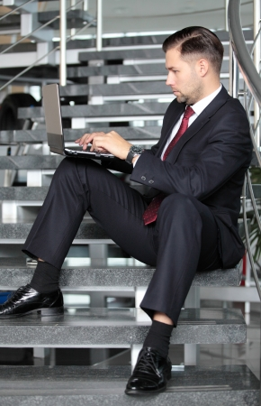 Handsome businessman sitting on the stairs and using his laptop - profile photo