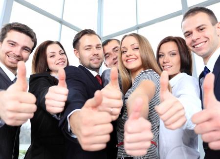 기호 엄지 손가락을 보여주는 성공적인 젊은 비즈니스 사람