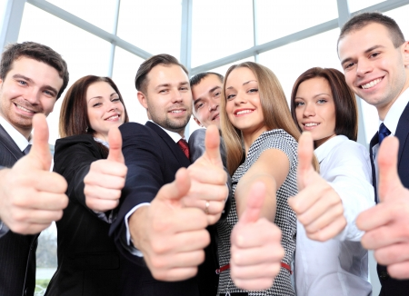 group goals: Successful young business people showing thumbs up sign