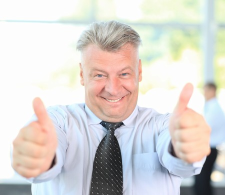 Portrait of confident mature businessman giving you thumbs up photo