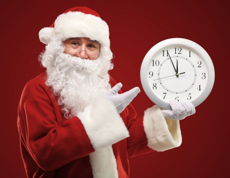 Photo of Santa pointing at clock showing five minutes to midnight photo