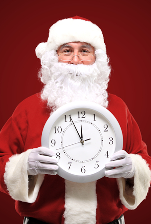 Santa pointing at clock showing five minutes to midnight photo