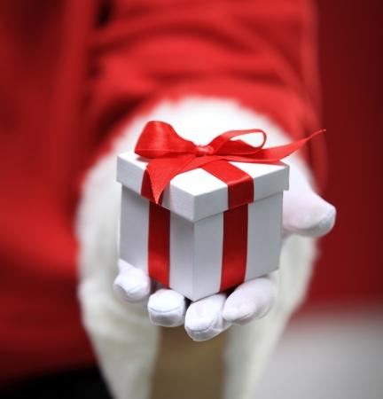 산타 클로스는 흰색있는 giftbox를 들고 손을 장갑 낀