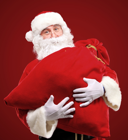 Portrait of Santa Claus embracing huge red sack with gifts photo