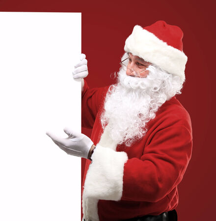 Happy Santa Claus looking out from behind the blank sign isolated on red with copy space photo