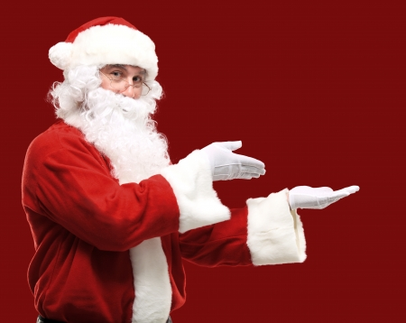 Santa Claus with his arms out in a presenting gesture. Isolated design element photo