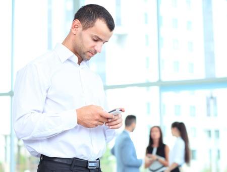 스마트 폰을 사용하는 잘 생긴 사업가. 사업가 현대 사무실 건물 내부에 서있는 휴대 전화를 찾고 스톡 콘텐츠