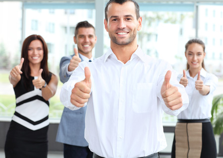 business concept - attractive businessman with team in office showing thumbs up