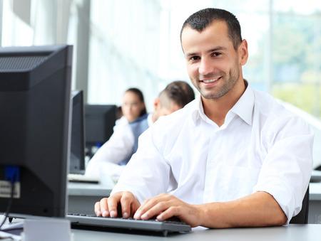 キーボードで入力して、机に座ってオフィスでラップトップを使用してカジュアルなビジネスマン