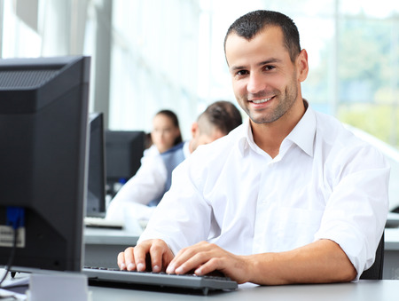 Casual businessman using laptop in office, sitting at desk, typing on keyboard  Stock Photo
