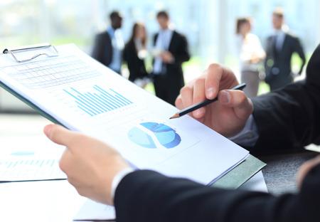 会議での議論の中にビジネス ドキュメントを指している男性の手の画像
