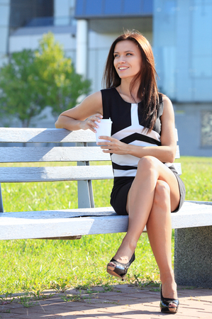 Portrait of an attractive young professional woman drinking coffee from disposable paper cup while sitting on a wooden bench in a park, smiling  Stock Photo