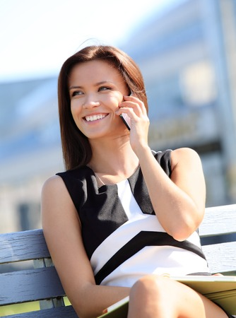 sitting on a bench: Young businesswoman having a conversation using a smartphone on a phone call while sitting on a city park bench, smiling