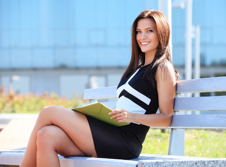 sitting on a bench: Portrait of an attractive young professional woman sitting on a wooden bench in a park, smiling.
