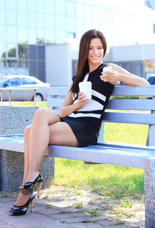 sitting on a bench: Portrait of an attractive young professional woman drinking coffee from disposable paper cup while sitting on a wooden bench in a park, smiling. Stock Photo