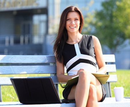 sitting on a bench: Young business woman sitting on a park bench and using laptop outdoors
