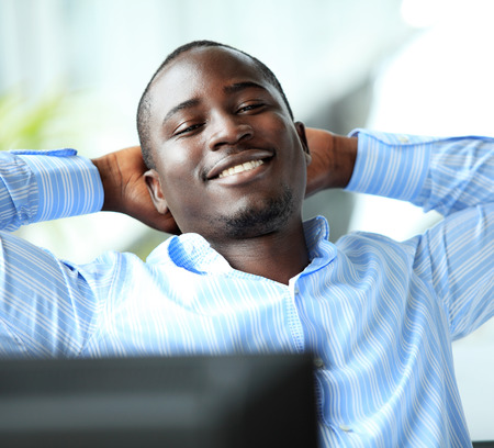 Portrait of a relaxed businessman looking away  african american businessman daydreaming in office  photo
