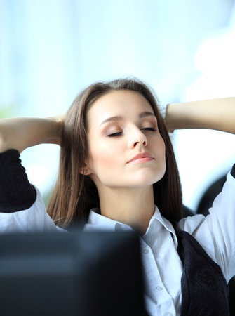 Portrait of an elegant cheerful woman relaxing in office photo
