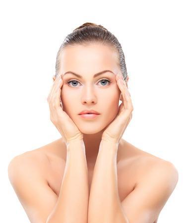 productos naturales: Muchacha hermosa que toca su cara. Aislado en un fondo blanco. Perfect Skin. Cara de belleza. Maquillaje Profesional Foto de archivo