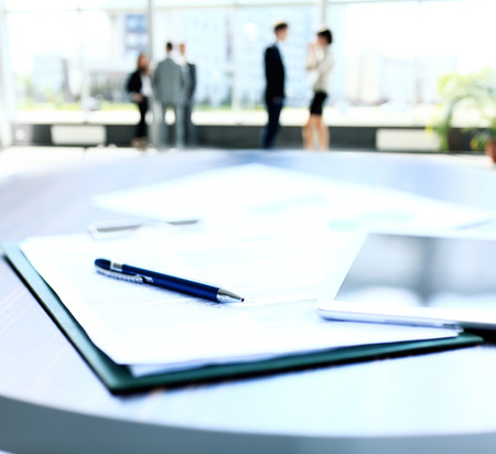 foreground focus: Close-up of business document in touchpad lying on the desk, office workers interacting in the background