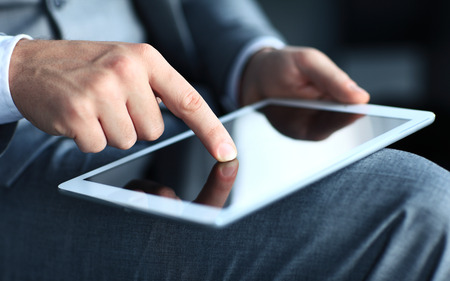 Close-up image of an office worker using a touchpad to analyze statistical data  Stock Photo