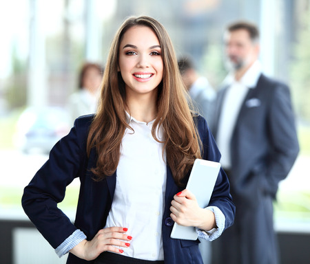 business hands: Business woman standing in foreground with a tablet in her hands, her co-workers discussing business matters in the background  Stock Photo