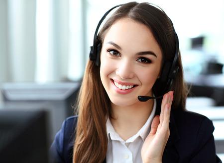 Operador de atención al cliente femenino con auriculares y sonriendo Foto de archivo
