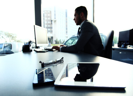 Silhouette of businessman using laptop in office  photo