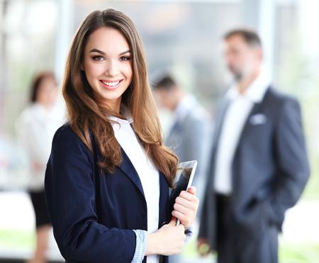 그녀의 손에 태블릿 전경에 서있는 비즈니스 우먼, 백그라운드에서 비즈니스 문제를 논의 그녀의 동료
