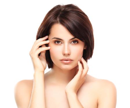 productos naturales: Muchacha hermosa que toca su cara aislada en un fondo blanco Perfect Skin Beauty Face maquillaje profesional