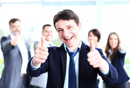 비즈니스 개념 - 엄지 손가락을 보여주는 사무실에서 팀과 함께 매력적인 사업가