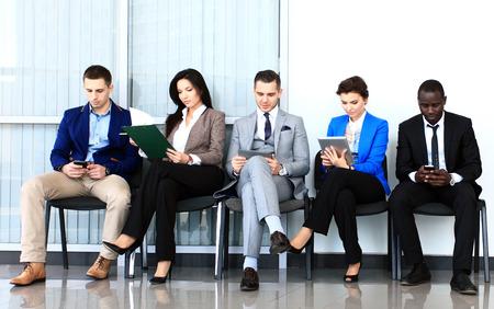 La gente de negocios de espera para la entrevista de trabajo Cinco candidatos compiten por una posición