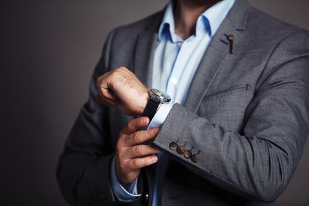 Zakenman die tijd controleert op zijn horloge mannen s hand met een horloge