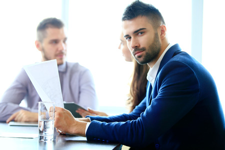 busy beard: Handsome businessman in casual working in office on background of his partners